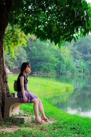 girl sit: Cute Thai girl is sitting alone under the tree, near the river bank in the rural area of Thailand  Stock Photo