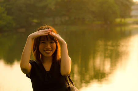 Cute Thai girl in the shade of sunset with a river background   photo