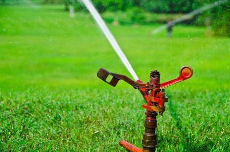 spattering: A metal automatic water sprinkler in the vast field Stock Photo