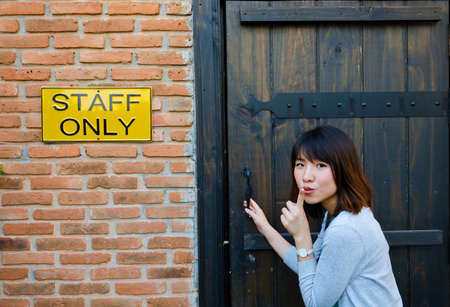 Cute Thai woman is trying to enter the staff room, which is a forbidden area. Stock Photo - 17253162