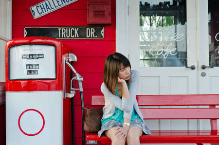 abandoned gas station: Cute Thai girl is waiting on the bench  of gas station