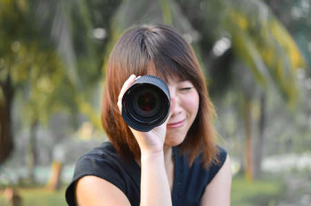 Cute Thai girl is putting camera lens on her eye Stock Photo - 17253156