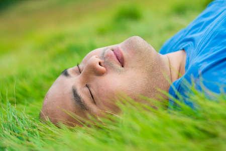 paz interior: El hombre tumbado en la hierba verde suave y relajante con placer Foto de archivo