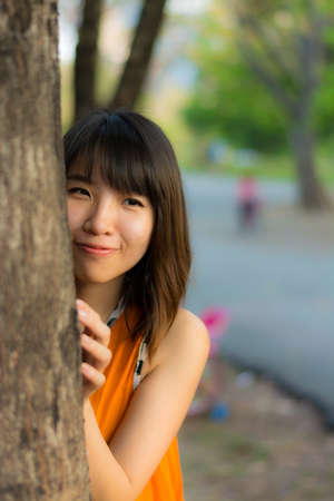 hide and seek: Cute Thai girl hiding behind the tree   Stock Photo