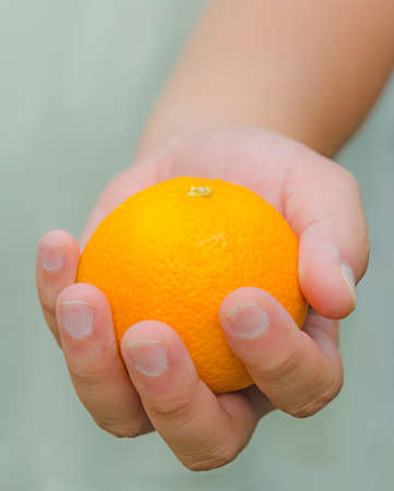 Here is an orange for you. A person is handing an orange for you. Stock Photo - 18198744