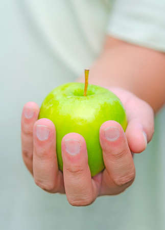 peal: Here is an apple for you. A person is handing green apple for you.
