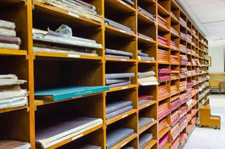 storeroom: Shelf of old worn out books and documents pile up together in Thailand library