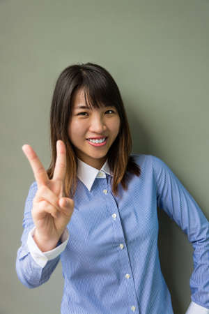girl shadow: Asian office girl showing cute vitory sign in grey background