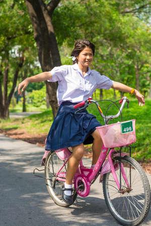 zapatos escolares: Colegiala tailandesa juego arriesgado en una bicicleta en el parque