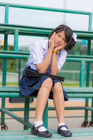 Shy Thai schoolgirl sitting on a metal stand photo