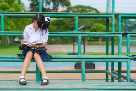 Cute Thai schoolgirl is sitting and reading on a metal stand photo