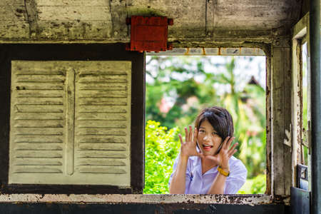 hide and seek: Cute Thai schoolgirl is making a surprise through the old window panel. Will anyone get frighten? Stock Photo