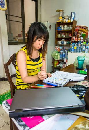 Thai college girl jest zajęty nauką w brudny biurko z koncentracją.