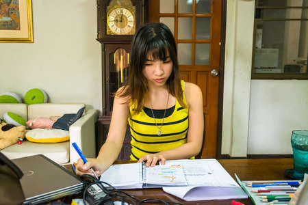 Thai college girl is busy studying in a messy desk with concentration. photo