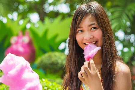 algodon de azucar: Linda chica tailandesa se est? comiendo algod?n de az?car de color rosa con alegr?a en la sombra en el verano Foto de archivo