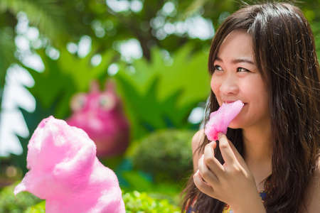 Cute Thai girl is eating pink candyfloss with joy in the summer shade Stock Photo - 19732057