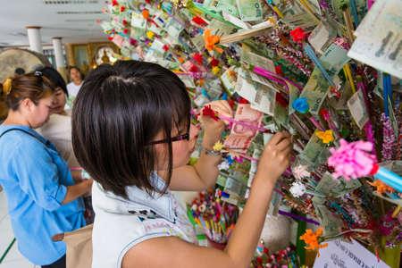 donates: BANGKOK, THAILAND - 24 MAY 2013  Thai Buddhist woman donates banknote in donation tree on May24, 2013 for Visakha Bucha day  Visakha Bucha day is the great Buddha