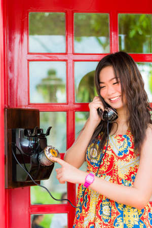 Thai girl is talking with an old-fashion phone in the telephone booth Stock Photo - 19856476