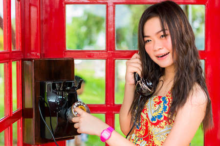 Thai girl is talking with an old-fashion phone in the telephone booth photo