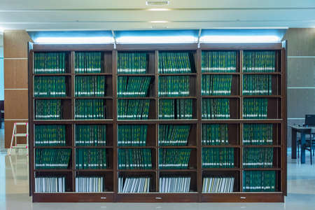 thesis: Row of green thesis in the large bookshelf in Chulalongkorn university of Thailand. It is full of Master degree knowledge.
