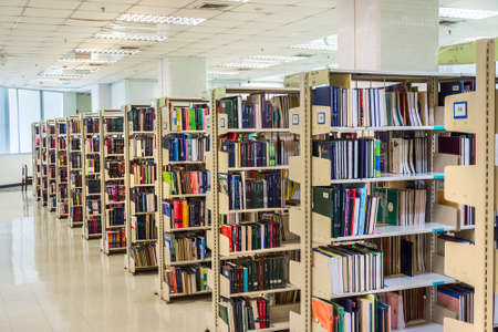 thesis: Row of textbooks in the large bookshelf in Chulalongkorn university of Thailand. It is full of Master degree knowledge. Editorial