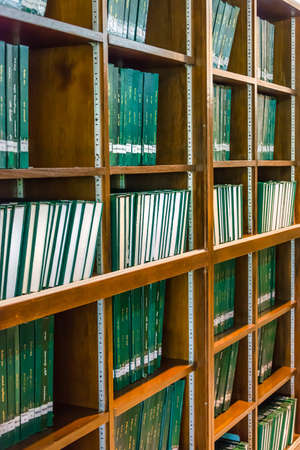master degree: Row of green thesis in the large bookshelf in Chulalongkorn university of Thailand. It is full of Master degree knowledge.