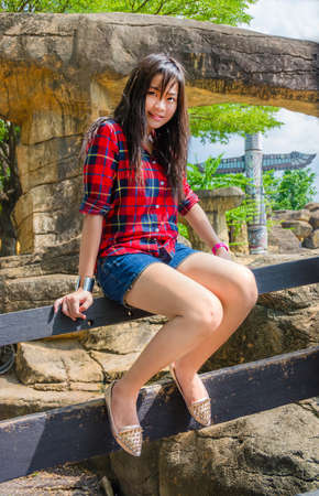 the totem pole: Cute Thai girl is sitting on the wooden fence in outdoor Stock Photo
