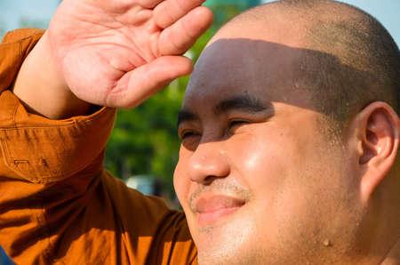 sonne: Eine Glatze Mann schützt seine Augen vor Sonnenlicht in die globale Erwärmung Situation