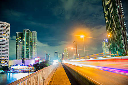 Main Highway of Bangkok at midnight with traffic lights and surrounding buildings photo