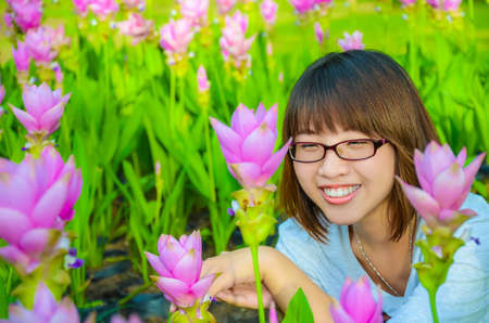 Cute Thai girl is very happy with flowers  Siam Tulip  in final retouch  She is laughing with joy  photo