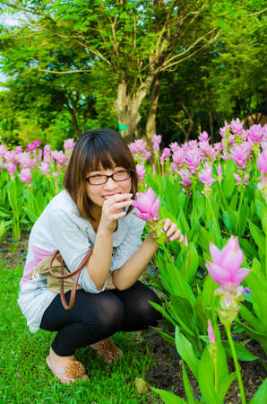 asian tulips: Cute Thai girl sneaking to pickup the pink Siam Tulip in the forbidden field