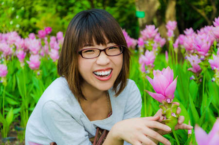 asian tulips: Cute Thai girl is very happy with flowers  Siam Tulip  in final retouch  She is laughing with joy
