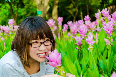 Cute Thai girl scent a pink Siam Tulip in final retouch  She loves flowers  Stock Photo - 21058766