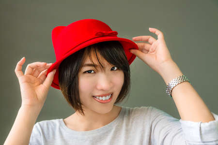 Thai girl is wearing her red hat showing cute gesture Stock Photo - 21188322