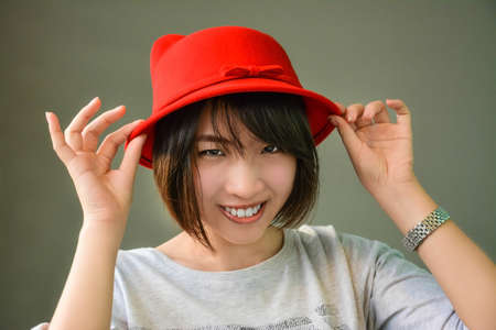 Thai girl is wearing her red hat showing cute gesture Stock Photo - 21188323