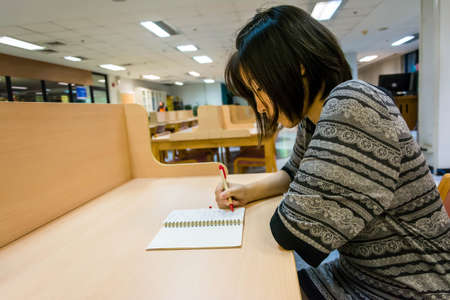 Thai college girl is writing her diary note on a clean desk Stock Photo - 21212793