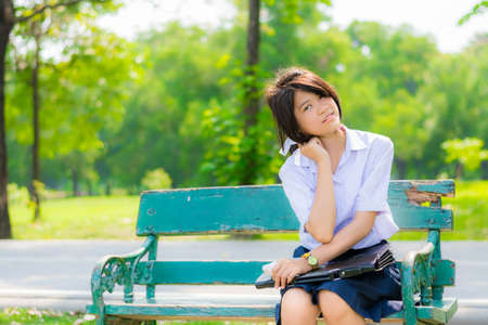 Shy Thai schoolgirl sitting on a bench in the park  closeup  photo