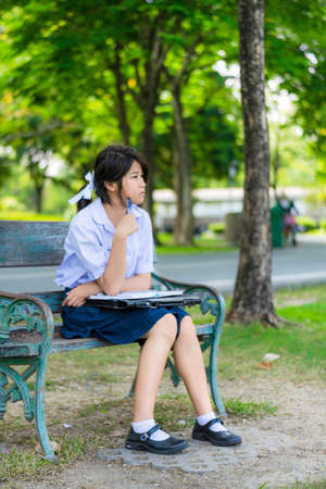 Cute Thai schoolgirl is sitting and studying on a bench photo
