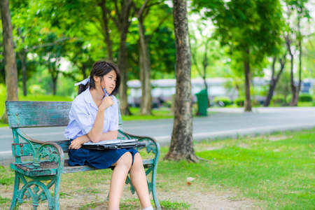 free thinking: Cute Thai schoolgirl is sitting and studying on a bench Stock Photo
