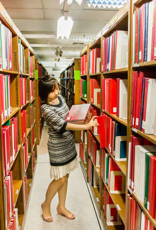 thesis: Thai  Master degree college girl is selecting a red hardcover thesis from the shelf in the university of Thailand