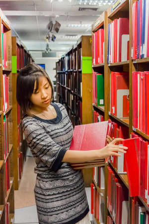 master degree: Thai Master degree college girl is selecting a red hardcover thesis from the shelf in the university of Thailand Editorial
