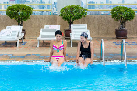 Two Asian girls are splashing water with their legs on the swimming pool photo