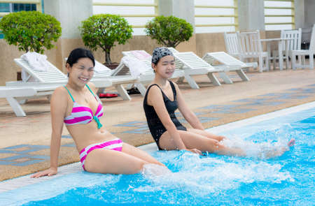 swimming costumes: Two Asian girls are splashing water with their legs on the swimming pool