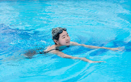 An Asian girl is swimming in the blue clean water of the swimming pool Stock Photo - 21492131