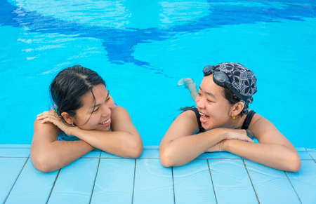 Two Asian girls are chatting in the swimming pool in holiday relaxation photo