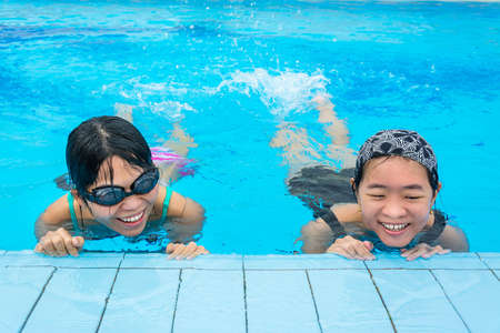 Two Asian girls are floating in the swimming pool by splashing their legs for warming up Stock Photo - 21964286