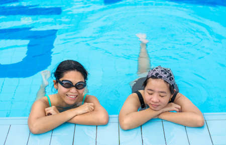 Two Asian girls are relaxing in the swimming pool corner for holiday photo