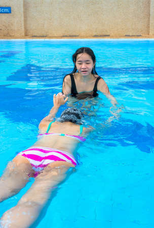 swimming costumes: An Asian girl is teaching another to swim in the swimming pool