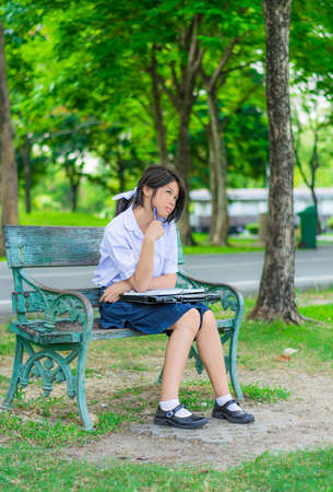 Cute Thai schoolgirl is studying and imagine something on a bench, letting her mind flow with imagination  photo