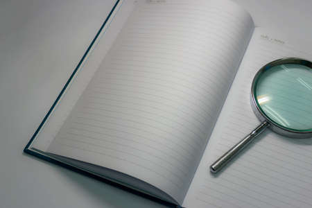 dim light: Still life notebook and magnifying glass in dim light